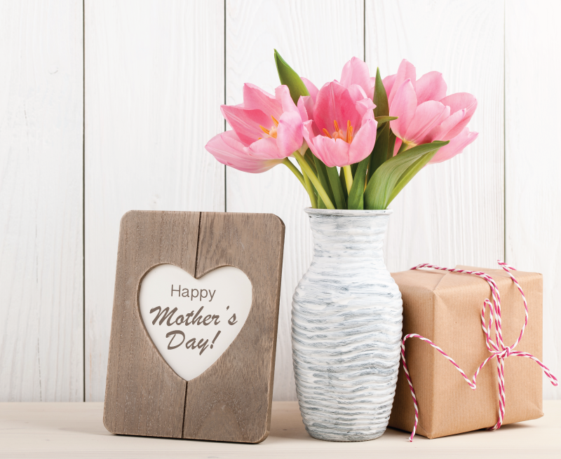 Pink tulip flowers with Mothers Day sign and Mother's Day gift.